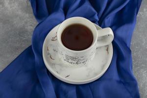 una tazza di ceramica bianca su una tovaglia blu foto