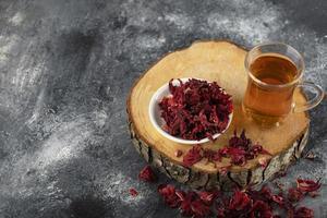 una tazza di tè caldo con fiori rossi secchi su un pezzo di legno foto