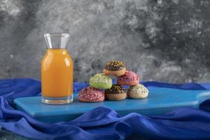 una bottiglia di vetro di succo con ciambelle colorate foto