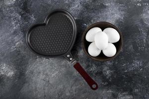 ciotola di uova bianche accanto a una padella a forma di cuore foto