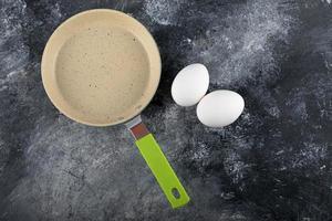 uova bianche crude accanto a una padella vuota foto