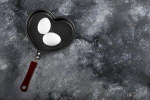 due uova bianche su una padella a forma di cuore foto