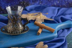 bicchiere vuoto e bastoncini di cannella su un bordo blu foto