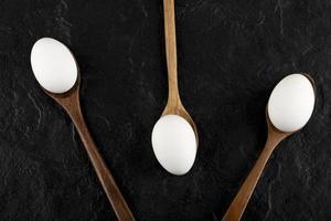uova bianche crude su cucchiai di legno foto
