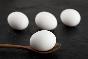 uova bianche crude e un cucchiaio di legno su uno sfondo nero foto