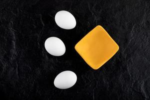 uova bianche crude e una piccola ciotola su uno sfondo nero foto
