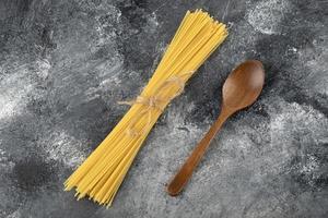 spaghetti secchi e un cucchiaio di legno su uno sfondo di marmo foto