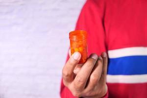 mano della persona che tiene il contenitore della pillola isolato su bianco foto