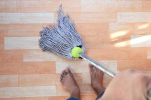 uomo che pulisce un pavimento di legno foto