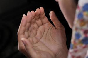 Close up della donna che prega su sfondo nero foto