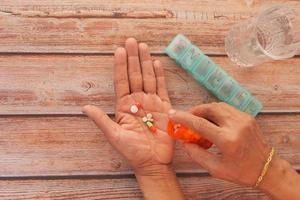 donna che prende la medicina quotidiana su sfondo neutro foto