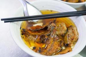 bun cha con maiale alla griglia, spaghetti di riso, verdure e zuppa nella cucina vietnamita foto