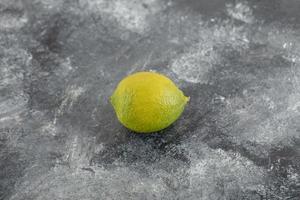 un limone maturo verde su uno sfondo di marmo foto