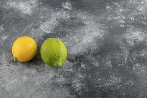 limoni gialli e verdi su fondo di marmo foto