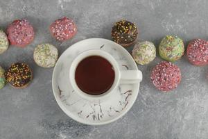 ciambelle dolci colorate con una tazza di tè foto