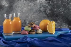 ciambelle dolci colorate con vasetti di vetro di succo e frutta a fette foto