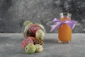 un barattolo di vetro pieno di piccole ciambelle colorate con una bottiglia di vetro di succo d'arancia foto