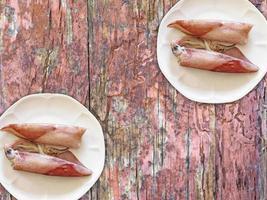 calamari sulla zolla bianca sul fondo della tavola in legno foto