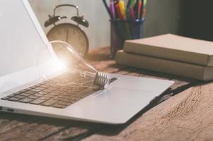 una lampadina accanto a un computer portatile, un nuovo concetto di idee foto