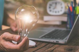 una persona in possesso di una lampadina accanto a un computer portatile, un nuovo concetto di idee foto