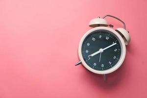 vecchia sveglia su sfondo rosa foto
