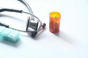 stetoscopio e contenitore di pillole su sfondo bianco foto