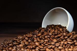 chicco di caffè che versa da una tazza bianca sulla tavola di legno foto