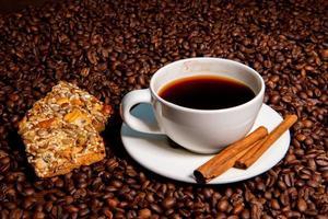 tazza di caffè bianco, bastoncini di cannella e biscotti sullo sfondo di chicchi di caffè foto