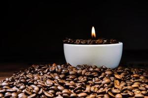 tazza di caffè bianco piena di chicchi di caffè e candela accesa in cima alla pila di chicchi di caffè foto