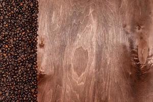 strisce di chicchi di caffè su sfondo texture in legno scuro, copia spazio per il testo foto