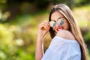 ritratto all'aperto di bella, emotiva, giovane donna in occhiali da sole foto