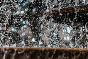 un primo piano di una spruzzata d'acqua con una ghirlanda di Natale in uno sfondo sfocato foto