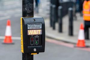 pulsante di attraversamento pedonale per pedoni con spia luminosa su uno sfondo sfocato foto
