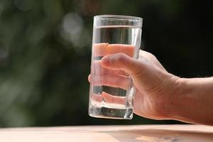 acqua potabile minerale sul tavolo di legno e acqua in vetro foto