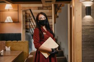 un manager in guanti medicali usa e getta neri indossa una maschera medica che tiene un menu in legno in un ristorante foto