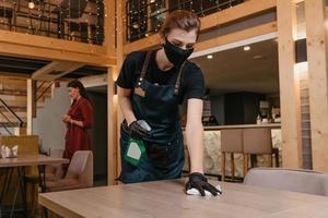 una cameriera gentile che indossa una maschera medica nera e guanti medici usa e getta tiene in mano una bottiglia con disinfettante e pulisce i tavoli con uno straccio in un ristorante foto