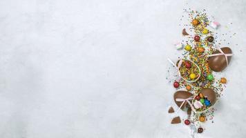 banner di Pasqua con uova di cioccolato e granelli di zucchero decorativi su uno sfondo grigio marmo
