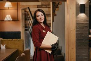 un direttore di ristorante femminile sorridente in guanti medicali monouso neri in possesso di un menu in legno in un ristorante foto
