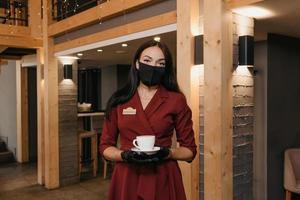 una donna manager di un ristorante indossa una maschera nera e guanti usa e getta in possesso di una tazza di caffè in un ristorante foto