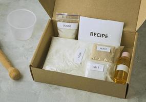 un set di ingredienti per cuocere il pane fatto in casa, tra cui farina integrale, sale, zucchero, girasole o olio d'oliva e lievito