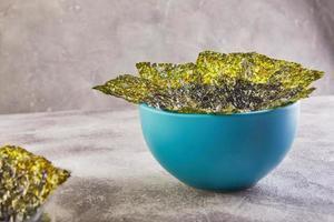 alghe nori croccanti in una ciotola blu su sfondo grigio foto