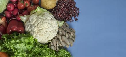 prodotti per una dieta detox vegetariana a base di cavolfiore, lattuga, ravanelli, pomodori, funghi, fagioli e peperone rosso su sfondo blu foto