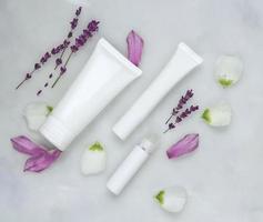 sfondo cosmetico per la cura della pelle di capsule di Petri e tubi cosmetici di erboristeria con foglie verdi e petali foto