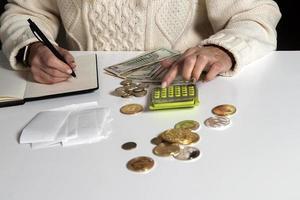 primo piano di una donna che calcola i soldi e scrive in un taccuino foto