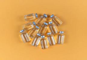 molte fiale con medicina liquida su sfondo giallo foto