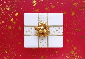 confezione regalo bianca con fiocco dorato e stelle su fondo rosso foto