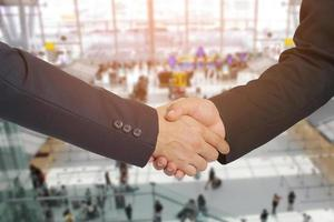 stretta di mano tra due uomini d'affari in un aeroporto, concetto di affari foto