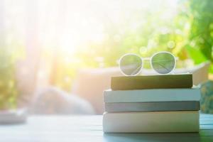 libri su un tavolo con occhiali da sole in cima in una camera resort in vacanza, lettura e concetto di educazione terapia rilassante foto