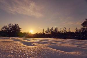 neve in primo piano in una gelida sera d'inverno al tramonto foto