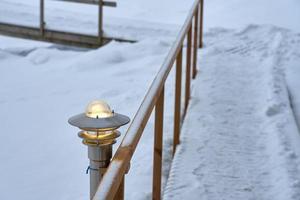 lanterna su un sentiero innevato con ringhiere in legno in inverno foto